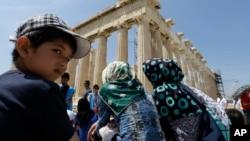 کودک پناهجوی افغان در مقابل یک معبد قدیمی ۲۵۰۰ ساله در یونان