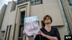 一個記者2017年6月19日在伊斯坦布爾法院外拿著受審記者亞梅特•艾坦的照片。