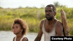 "Quvenzhane Wallis as ""Hushpuppy"" and Dwight Henry as ""Wink"" on the set of Beasts of The Southern Wild (Photo: Fox Searchlight / Mary Cybulski)"