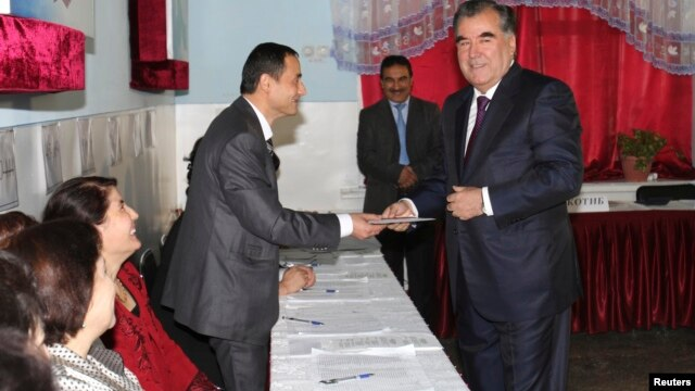 Tajikistan's President Imomali Rakhmon (R) receives his ballot from an electoral official during the presidential election in Dushanbe, in this Nov. 6, 2013 handout photograph provided by Press Service of presidential administration of Tajikistan.