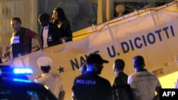 FILE - A migrant disembarks escorted by police from Italy's Diciotti coast guard vessel carrying 67 asylum seekers berthed at Trapani port on July 12, 2018.