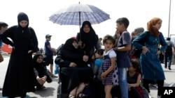 Seorang perempuan migran memayungi perempuan tua yang duduk di atas kursi roda setibanya di pelabuhan Piraeus, Athena dari Lesbos, Yunani (Foto: dok).