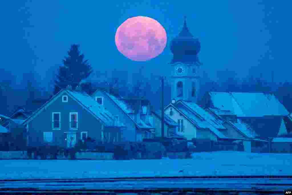 A full moon sets behind the parish church of Schoenach near Regensburg, southern Germany.