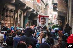ບັນດາຜູ້ສະໜັບສະໜູນ ອະດີດປະທານາທິບໍດີ ຜູ້ຖືກໂຄ່ນລົ້ມ ທີ່ນັບຖືສາສະໜາອິສລາມ ທ່ານ Mohamed Morsi, ຮ້ອງໂຮຄຳຂວັນ ແລະ ຊູຮູບຂອງທ່ານ Morsi ພາຍຫຼັງທີ່ພັກພະລາດອນພາບ ມູສລິມ ຮຽກຮ້ອງໃຫ້ບັນດາຜູ້ສະໜັບສະໜູນຂອງຕົນ ອອກມາເດີນຂະບວນ ເນື່ອງໃນວັນຄົບຮອບ ການລຸກຮືຂຶ້ນ ຂອງປີ 2011 ໃນນະຄອນ Cairo, ປະເທດອີຈິບ.