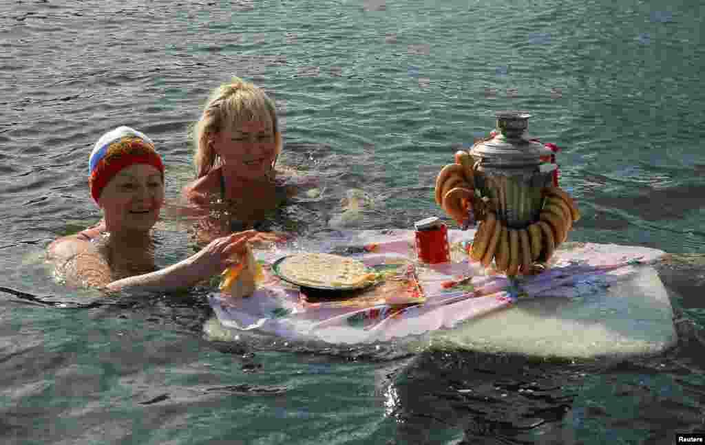 """آب بازی دو زن به همراه یک سماور و چندین """"پنکیک"""" در جشن """"ماسلنیتسا"""" یا """"هفته پنکیک"""" در شهر پودولسک روسیه."""