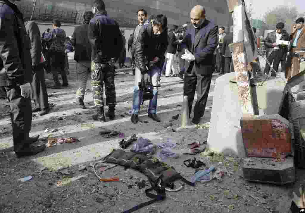 An Afghan cameraman films the vest of an attacker and arms collected from the scene of a suicide attack in Kabul, Afghanistan, ,November 21, 2012.