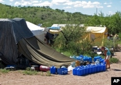 FILE - No More Deaths volunteer Katie Maloney checks water jugs at the group's camp, near Arivaca, Ariz., about 13 miles north of Mexico, before heading out to supply water stations for migrants illegally crossing the border.