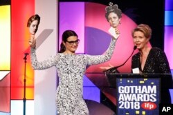 "Actress Rachel Weisz, left, holds photos of her co-stars Emma Stone and Olivia Colman from the movie ""The Favorite"" as she accepts a special honor from Cynthia Nixon at the 28th annual Gotham Awards, Nov. 26, 2018, in New York."