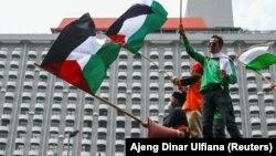 Sejumlah anggota organisasi buruh Indonesia memegang bendera Palestina saat melakukan aksi protes terhadap Israel di luar gedung PBB di Jakarta, 18 Mei 2021. (Foto: REUTERS/Ajeng Dinar Ulfiana)