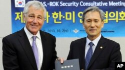 In this photo provided by the South Korean Defense Ministry, U.S. Secretary of Defense Chuck Hagel, left, poses for photos with his South Korean counterpart Kim Kwan-jin, Oct. 2, 2013.