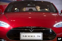 """FILE - A man sits in a Tesla Model S electric car on display at a Beijing auto show, April 25, 2016. In May, a Tesla on """"autopilot'' crashed into a truck that was turning, drawing attention to the limitations of self-driving technology."""