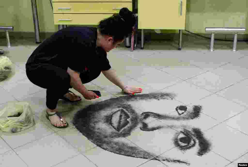 Hairdresser Svetlana Grozdanovska creates a celebrity's portrait on the floor of her salon using her clients' cut hair, in Krivogastani, North Macedonia.