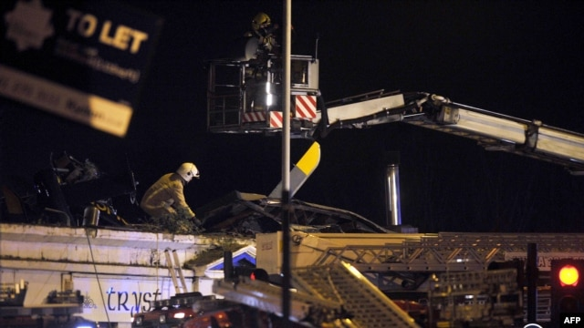 Emergency services inspect the roof of a pub where a police helicopter crashed in central Glasgow, Scotland, shortly after midnight on November 30, 2013.
