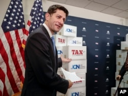 Speaker of the House Paul Ryan, R-Wis., points to boxes of petitions supporting the Republican tax reform bill that is set for a vote later this week as he arrives for a news conference on Capitol Hill in Washington, Nov. 14, 2017.