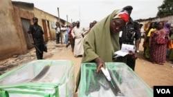 Seorang perempuan Nigeria memasukkan suara ke kotak suara di kota Kaduna (28/4).