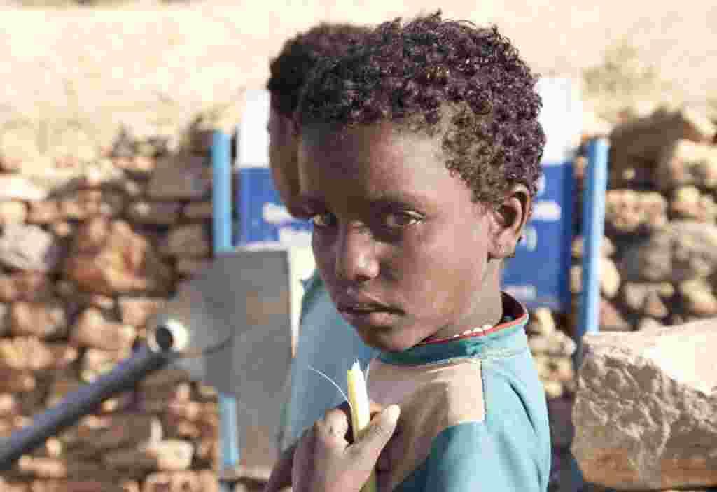 Una niña sostiene una caña de azúcar cerca de un pozo en Enda Selassie, Etiopía.