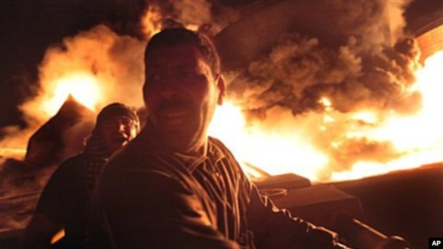 Libyan men react as the main fuel depot in Misrata burns after a bombing by pro-Gadhafi forces, May 7, 2011