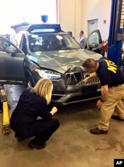 FILE - In this March 20, 2018, file photo provided by the National Transportation Safety Board, investigators examine a driverless Uber SUV that fatally struck a woman in Tempe, Ariz.