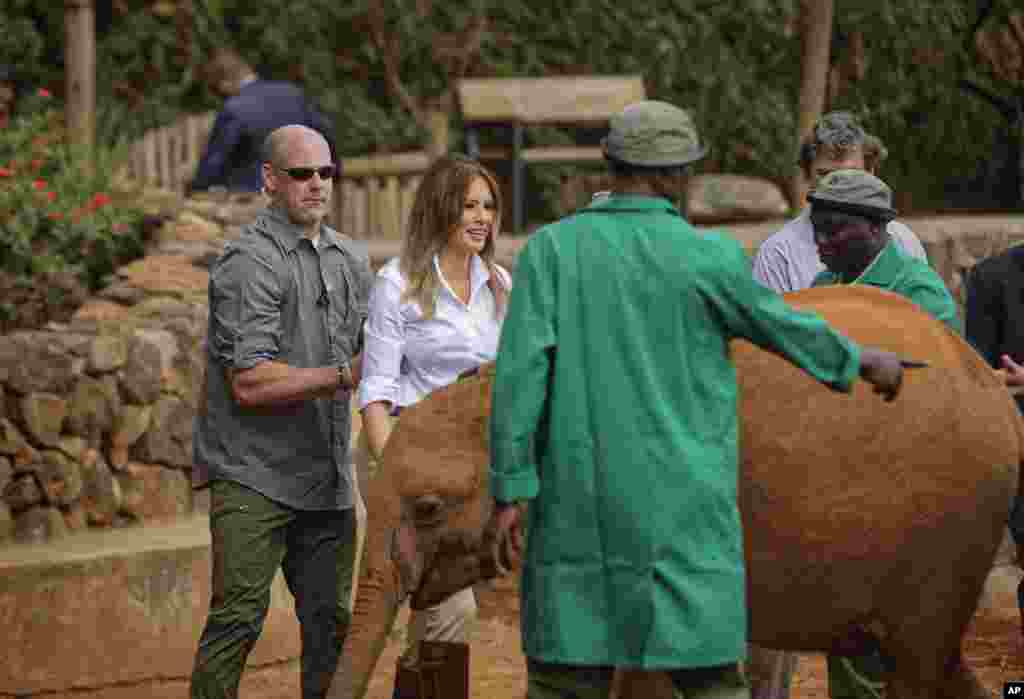 A Secret Service agent, left, holds U.S. first lady Melania Trump to protect her as she steps backwards after being nudged by a baby elephant she petted, at the David Sheldrick Wildlife Trust elephant orphanage in Nairobi, Kenya Oct. 5, 2018.