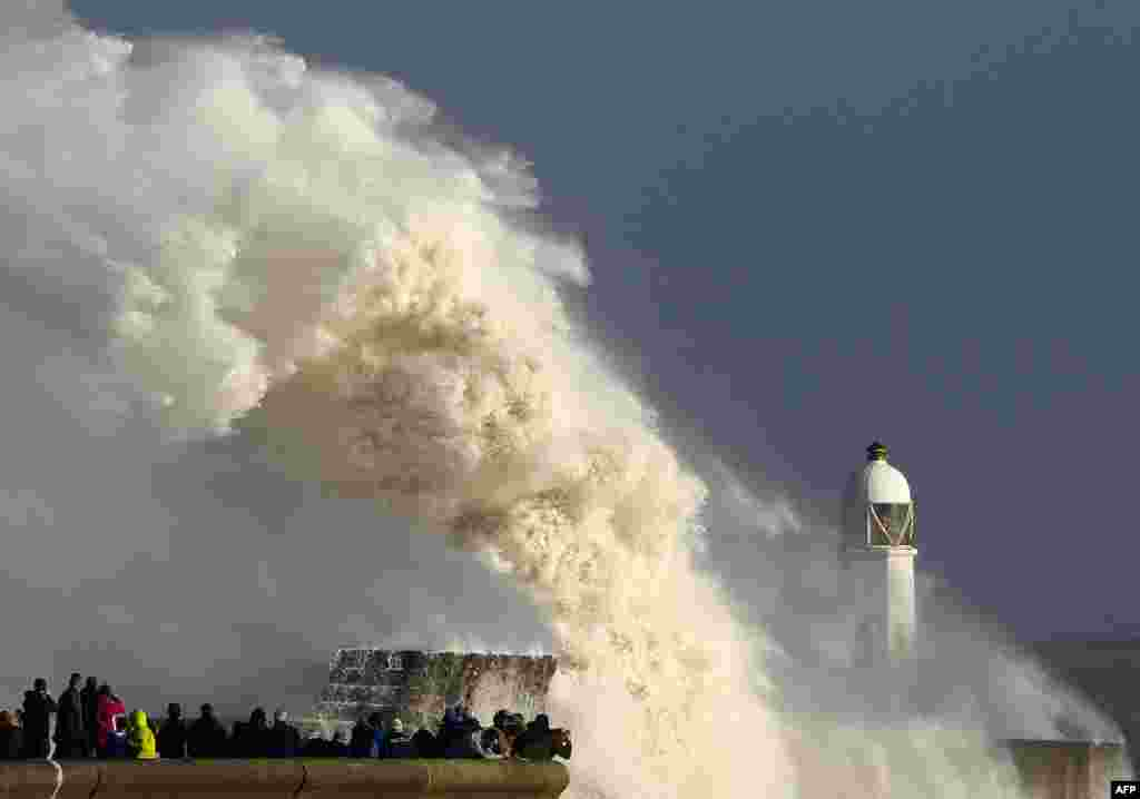 Huge waves strike the harbor wall and lighthouse at Porthcawl, south Wales, as Storm Ophelia hits the UK and Ireland.