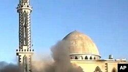 叙利亚霍姆斯市一个清真寺前面被炮击后浓烟滚滚的情景