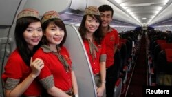 VietJet cabin crew members are seen inside a A320 airplane before departure for Bangkok, at Noi Bai international airport in Hanoi.