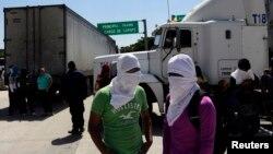 Estudiantes con las caras tapadas bloquean la ruta hacia Acapulco en las afueras de Chilpancingo, estado de Guerrero.