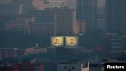 平壤纪念公园清晨时光中的朝鲜前领导人金日成和金正日的照片。