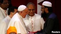Paus Fransiskus berjabat tangan dengan pemimpin Muslim Sri Lanka, Maulavi Ash-Sheikh M.F. M. Fazil dalam pertemuan lintas agama di Kolombo (13/1). (Reuters/Stefano Rellandini)