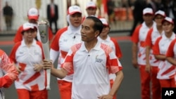 "Indonesian President Joko ""Jokowi"" Widodo, center, holds the Asian Games torch as he runs during an independence day ceremony at Merdeka Palace in Jakarta, Indonesia, Aug. 17, 2018. Critics say the president is growing increasingly authoritarian."