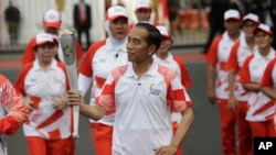 "Indonesian President Joko ""Jokowi"" Widodo, center, holds the Asian Games torch as he runs during an independence day ceremony at Merdeka Palace in Jakarta, Indonesia, Aug. 17, 2018."