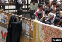 A woman takes photos of men from behind a barrier at Taghyeer (Change) Square where anti-government protesters have been camping for more than a year to demand regime change in Sanaa, April 10, 2012.