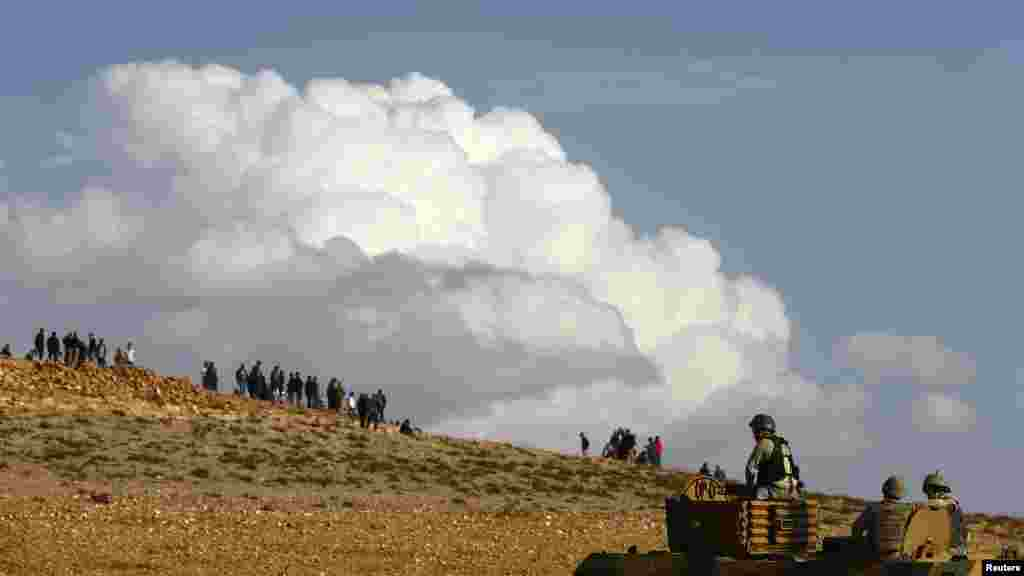 Turkish military look toward observers as they try to clear a hill near the Mursitpinar crossing on the Turkish-Syrian border, Oct. 26, 2014.