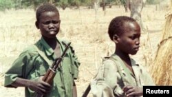 Two Sudanese boy soldiers keep watch outside a rebel military headquarters in remote southern Sudan Feb. 13, 2000. The Sudan People's Liberation Movement-North (SPLM-N) has agreed to end and prevent the recruitment and use of children in conflict.