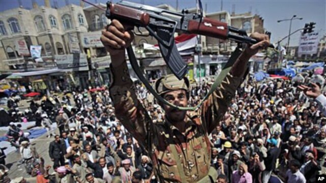 A Yemeni army officer holds up his AK-47 as he and other officers join anti-government protesters demanding the resignation of Yemeni President Ali Abdullah Saleh in Sanaa, Mar 21 2011