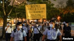 Police officers disperse people mourning at Victoria Park on the 32nd anniversary of the crackdown on pro-democracy demonstrators at Beijing's Tiananmen Square in 1989, in Hong Kong, China June 4, 2021.