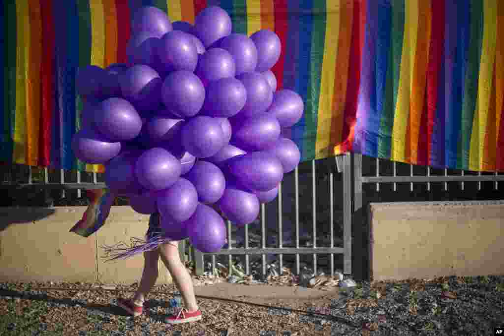 A woman holds balloons as she participates in the first Gay Pride Parade in Beersheba, Israel.