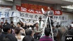 Một người đại đại diện dân làng Ô Khảm đứng trên thang nói chuyện với dân làng trong khi một cuộc biểu tình đang diễn ra