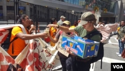 Volunteers hand out free water to protesters at an anti-Trump rally outside the Republican National Convention in Cleveland, Ohio, July 20, 2016. (W. Gallo/VOA)