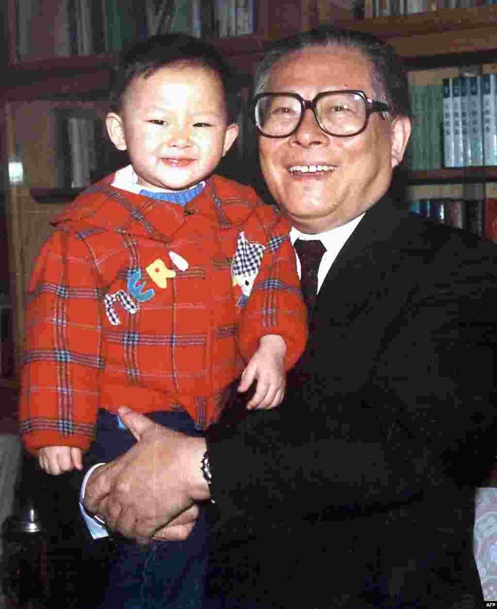 1990年代,中国国家主席江泽民在北京中南海的办公室抱着孙子。法新社说此图拍摄时间不详。本图集编辑估计是1990年代的照片。