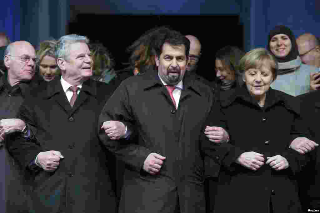 Bundestag President Norbert Lammert, German President Joachim Gauck, Chairman of the Central Council of Muslims in Germany Aiman Mazyek and German Chancellor Angela Merkel, link arms during a vigil organized by Muslim groups for the victims of the terror shooting by gunmen at the offices of Charlie Hebdo, in front of the Brandenburg Gate in Berlin, January 13, 2015.