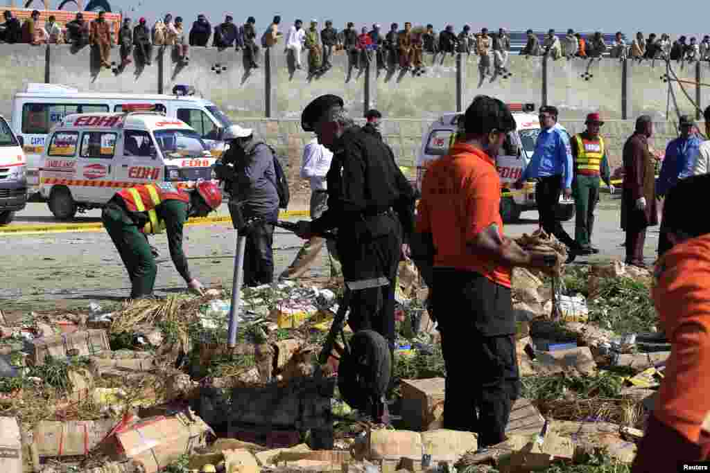 Security officials and rescue workers survey the site of a bomb blast at a vegetable and fruit market in the outskirts of Islamabad, April 9, 2014.