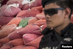 FILE - A police officer from the Narcotics Control Board guards bags of methamphetamine pills during a Destruction of Confiscated Narcotics ceremony in Ayutthaya province, north of Bangkok, Thailand. The significant organized crime threat involves not only narcotics but also human trafficking and wildlife smuggling.