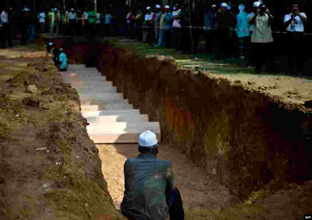 A Malaysian Muslim man sits near a pit during the re-burial of remains believed to be those of ethnic Rohingya found at human-trafficking camps in Kampung Tualang, some 16 kilometers east of Alor Setar. Authorities held a sombre mass funeral for 21 suspected ethnic Rohingya found in human-trafficking graves last month.