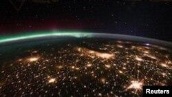 Wilayah Midwestern AS terlihat dari stasiun angkasa internasional dengan aurora borealis tampak di belakangnya (foto: ilustrasi).