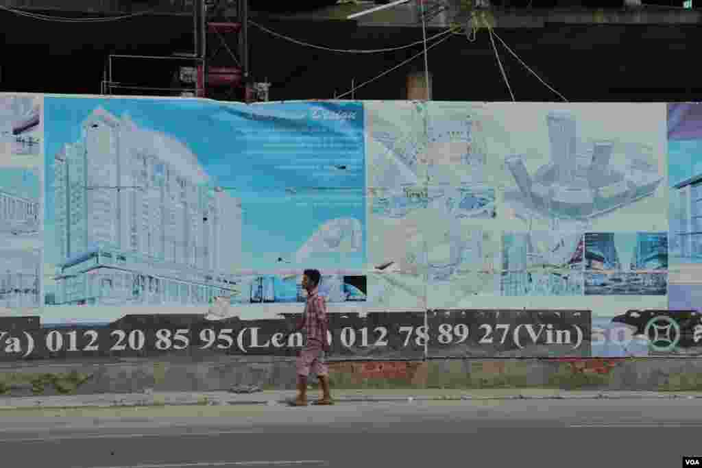 A passenger walks past an advertisement for Olympia City near its construction site. on September 29, 2014. (Nov Povleakhena/VOA Khmer)