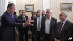 Russian Foreign Minister Sergey Lavrov, left, welcomes a delegation headed by a leader of the Syrian National Council, Abdulbaset Sieda, right, in Moscow, Russia, July 11, 2012.