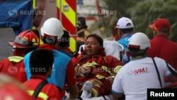 Un bombero es evacuado durante el incendio en el centro comercial Larcomar de Lima, Perú.