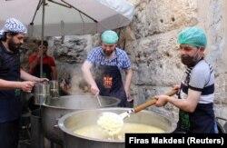 """Relawan dari organisasi amal """"Saed"""" menyiapkan makanan untuk dibagikan kepada orang-orang yang membutuhkan selama bulan suci Ramadhan, di Damaskus, Suriah, 23 April 2021. (Foto: REUTERS/Firas Makdesi)"""