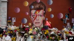 FILE - Tributes lie placed around a mural of British singer David Bowie by artist Jimmy C in Brixton, south London, Jan. 14, 2016.